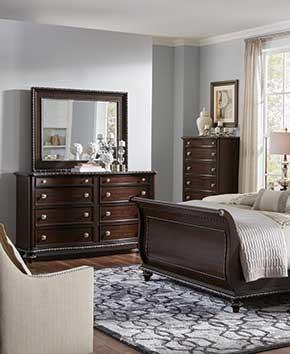 adult bedroom with dark wooden chests and dressers