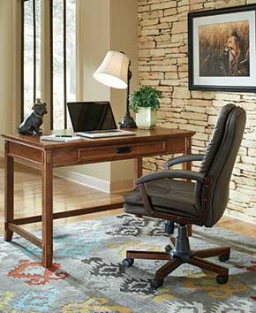 home office with light brown desk and dark brown rolling chair